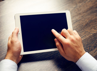 hands of a man holding blank tablet device