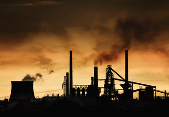 Smokestack in factory with yellow sky and clouds.  Pollution