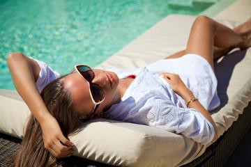 Sexy woman sunbathing at pool resort
