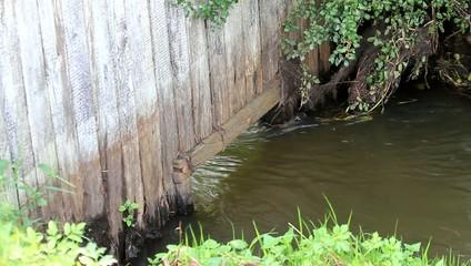 Wasser fließt im Bach unter Holzwand