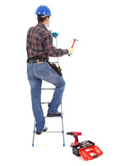 Carpenter with hammer on the stepladder