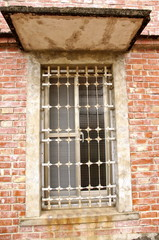 The closeup of window with iron bar grill