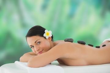 Beautiful brunette enjoying hot stone massage smiling at camera