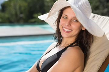 Beautiful woman relaxing by swimming pool