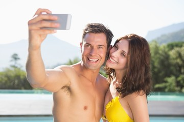 Couple taking picture of themselves by swimming pool