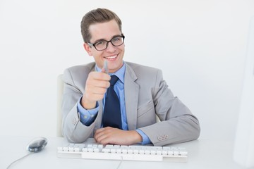 Nerdy businessman working on computer pointing at camera