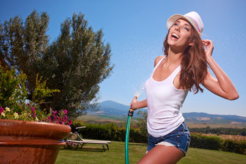 Happy sexy woman watering flowers in italy garden