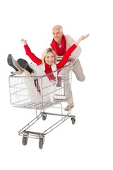 Happy couple messing about in shopping trolley
