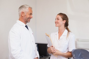 Dentist and dental assistant smiling at each other