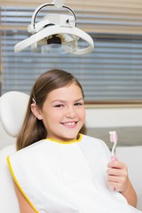 Little girl holding toothbrush in dentists chair