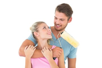 Young couple hugging and holding paint roller