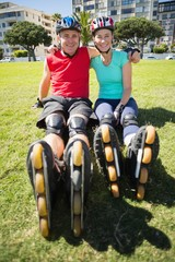 Fit mature couple wearing roller blades on the grass