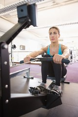 Young woman working on fitness machine at gym
