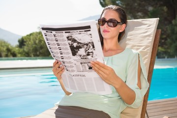 Woman reading newspaper on sun lounger by pool