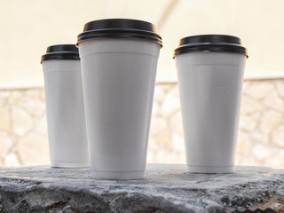 White disposable cups with black lids