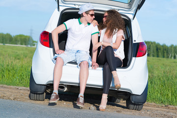 young couple sitting in the open trunk