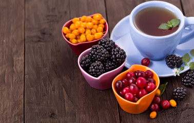 Various berries with cup of tea