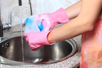 Young caucasian woman in protective gloves washing dishes.