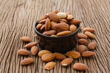 Almonds seed in black bowl on wooden background
