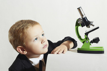 little scientist.Schoolboy with a microscope.child in suit