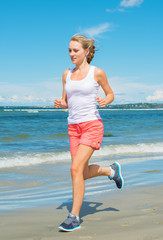 Sporty woman running along the beach.