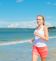 Sporty woman running along the beach. Place for text.