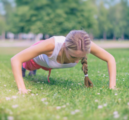 Pretty woman doing push-ups in the park.