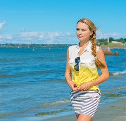 Beautiful young woman walking near the sea. Place for text.