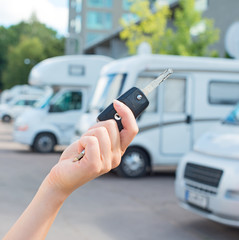 Woman's hand with key against campervans background.