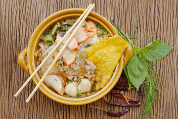 asian cuisine , pork noodle in the bowl with herb on wooden back