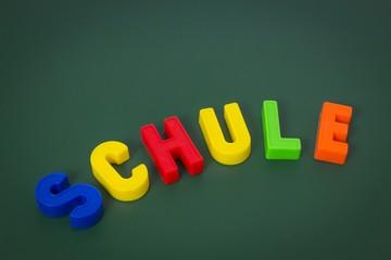 Schultafel mit bunten Schule-Buchstaben