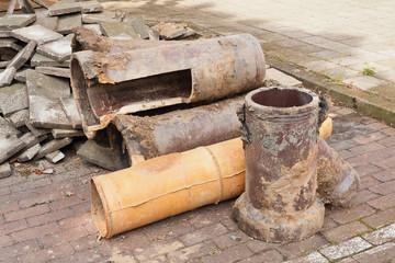 Alte Rohre aus Ton und Gehwegplatten aus Beton am Strassenrand
