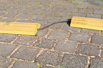 Ein Überfahrschutz aus gelbem Kunststoff schützt ein Kabel