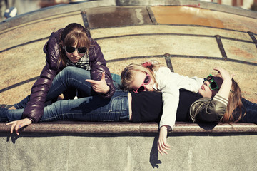 Group of teenage school girls lying on the sidewalk