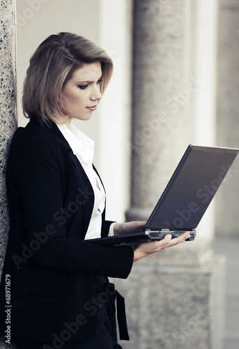 Young business woman with laptop at the office building