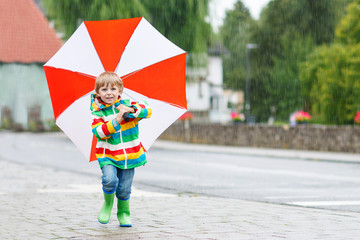 Beautiful child with yellow umbrella and colorful jacket outdoor