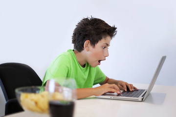 Gamer young boy is playing game on computer