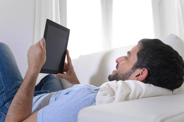 young attractive man using digital tablet sitting on couch