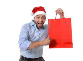 young handsome man wearing santa hat holding red shopping bag