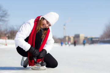 Happy young woman tying her ice skates in winter