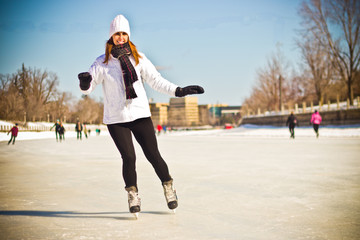 Attractive young woman ice skating during winter - retro filter