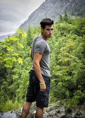Handsome young man hiking in lush green mountain scenery