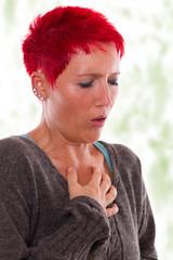 Frau mit Hustenanfall und Brustschmerzen