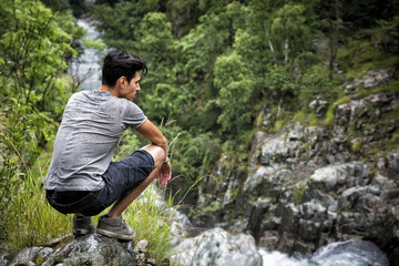 Handsome young man sitting in lush green mountain scenery