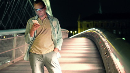 Young man texting on smartphone on the bridge in the city at nig