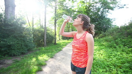 Beautiful Young Woman Drinking Water after Fitness Exercises