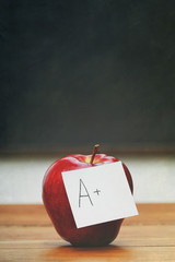 Red apple with note on desk with blackboard