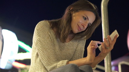 Woman with smartphone in the city at night