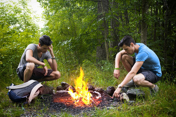 Two young men camping next to burning campfire