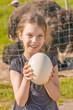 smiling girl holding ostrich egg